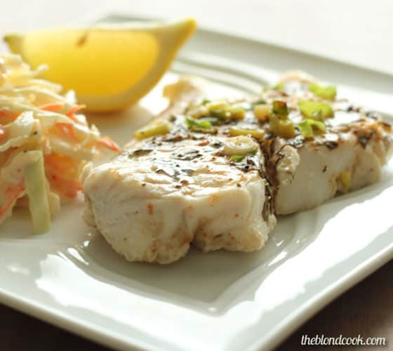 A closeup of baked fish, coleslaw and lemon wedge on a white plate.