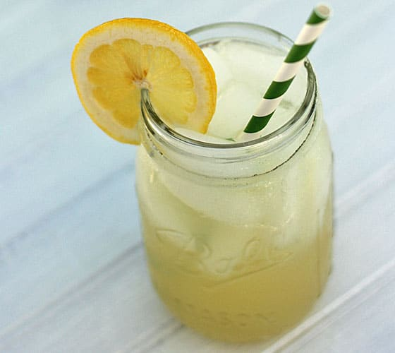 Lemonade cocktail in a mason jar with a green striped straw and lemon slice.