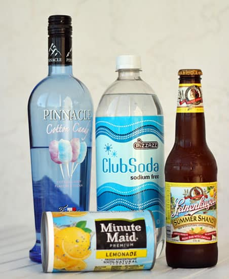 A bottle of vodka, club soda, a beer and lemonade concentrate.