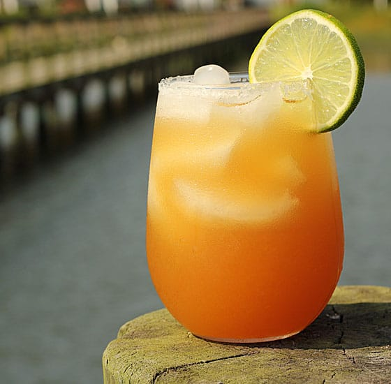An orange colored margarita garnished with lime with a water view in background.