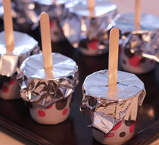 Small polka dot paper cups covered with foil. Popsicle sticks are stuck through the foil.