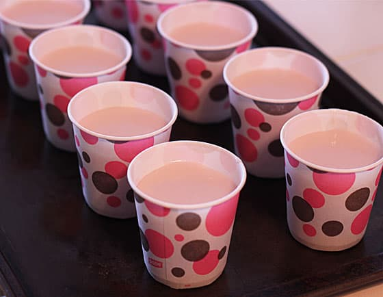 Small polka dot paper cups filled with popsicle mixture on a baking sheet.