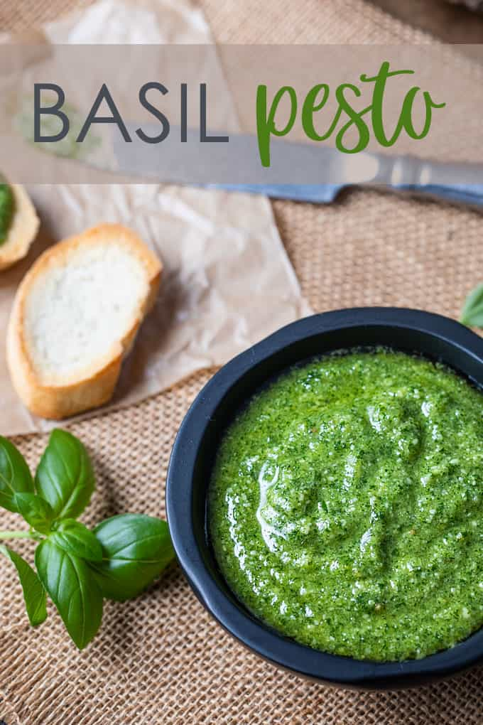 Basil pesto in a black bowl with French bread, fresh tomatoes and basil leaves.