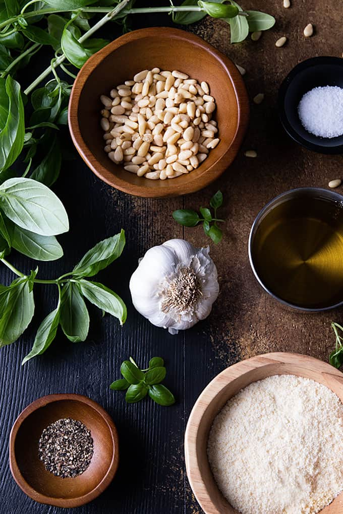 Ingredients for basil pesto: fresh basil, garlic, olive oil, salt, pepper, pine nuts and Parmesan cheese.