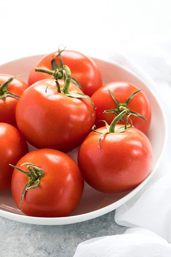 A round white bowl full of tomatoes to be used in tomato pie