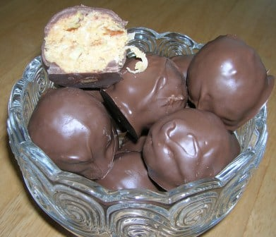 Chocolate peanut butter balls in a decorative clear glass bowl.