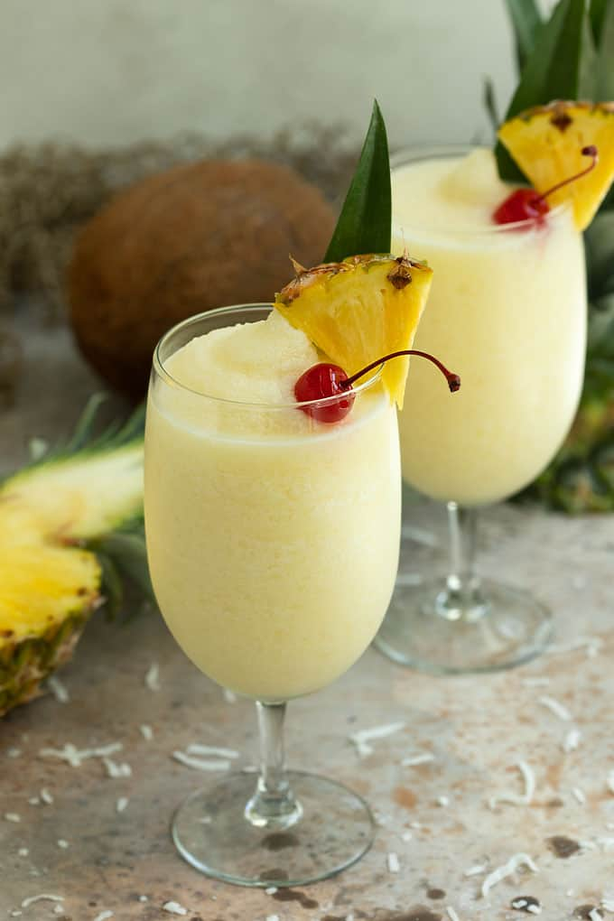 Front view of 2 glasses of frozen pina colada garnished with cherries and fresh pineapple