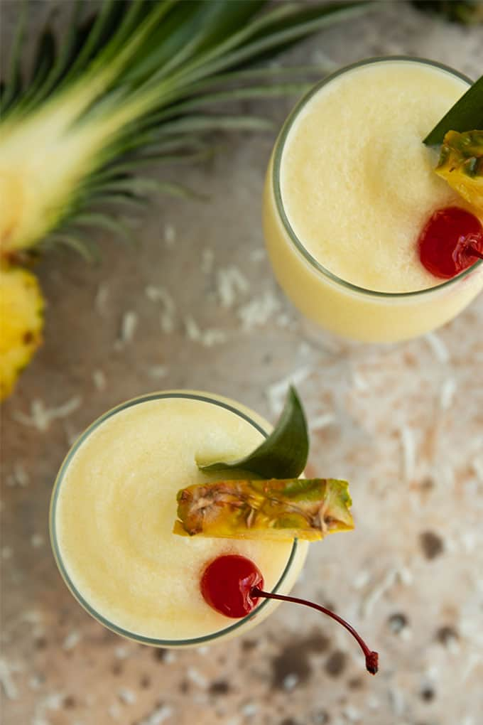 Overhead view of 2 glasses of pina colada drink beside a cut fresh pineapple