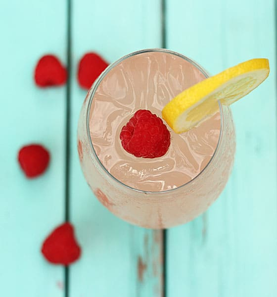 Overhead view of a pink cocktail in a glass garnished with lemon and raspberry.