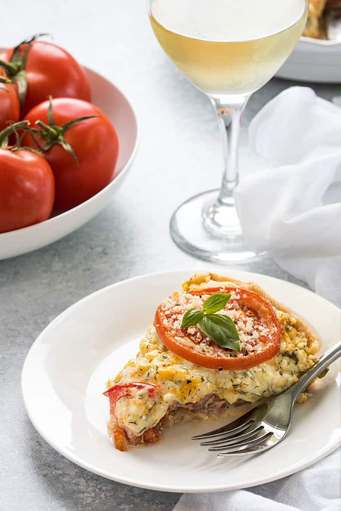 A slice of tomato pie on a round white plate with a fork and glass of white wine
