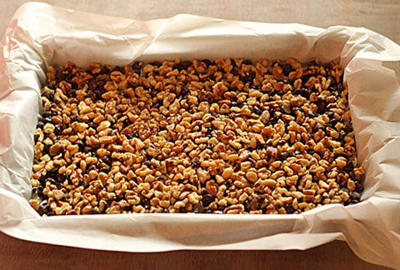Chocolate layer bars in a rectangle pan lined with parchment paper