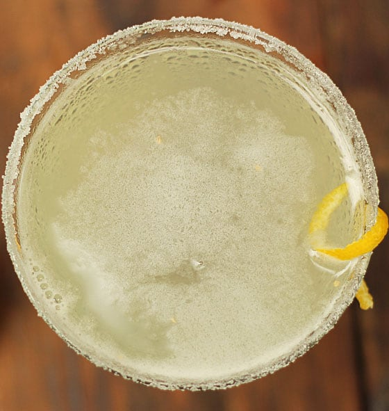 Overhead closeup of a martini in a glass rimmed with sugar and garnished with lemon peel.