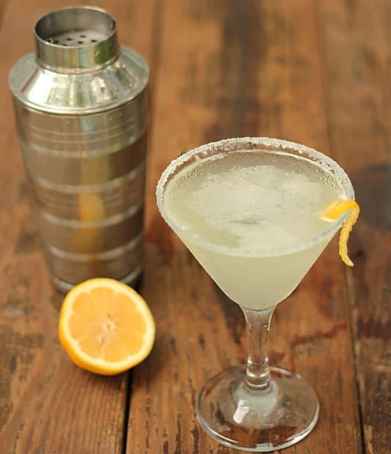 A martini in a glass rimmed with sugar and garnished with lemon peel.