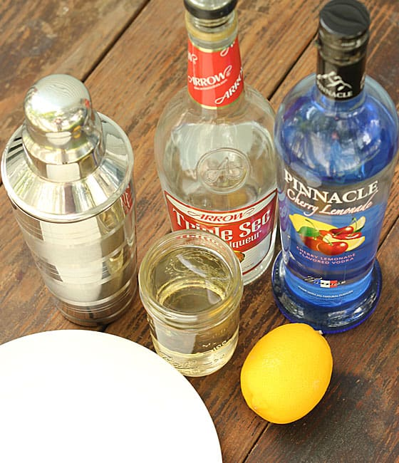 A cocktail shaker, bottles of orange liqueur, vodka, a glass with simple syrup and a lemon.