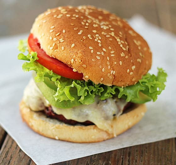 A cheeseburger with lettuce, tomato and an avocado slice on a sesame seed bun.