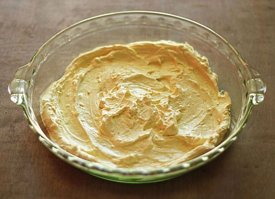 A clear round glass dish with a cream cheese and mayonnaise mixture.