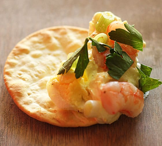 A round cracker with shrimp dip on it on a wooden surface.