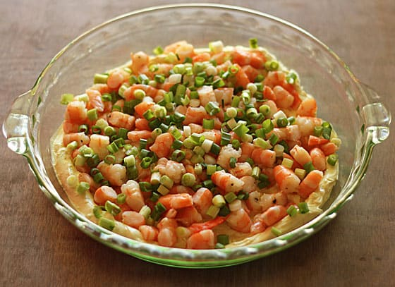 A round glass dish layered with a cream cheese mixture, shrimp and green onions.