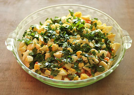 A round glass dish layered with ingredients.  Visible top layer is chopped boiled egg and chopped parsley.