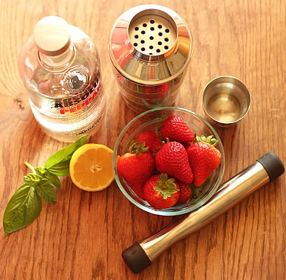 A bottle of vodka, cocktail shaker, strawberries, lemon, basil and a muddler.
