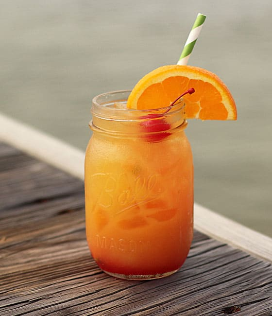 An orange cocktail in a jar on a wooden dock with water in the background.