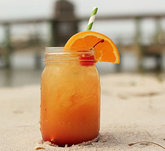 An orange cocktail in a jar garnished with an orange slice and cherry in the sand on a beach.