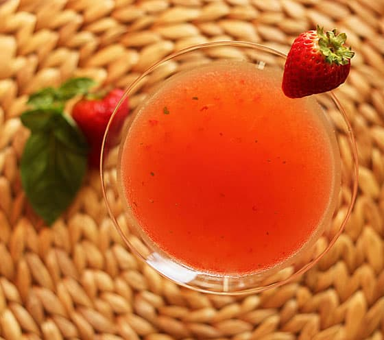 Overhead view of a strawberry martini with fresh basil pieces in it.