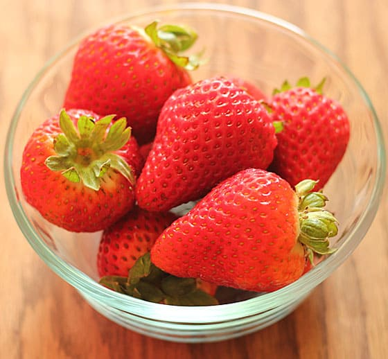 Fresh strawberries in a small glass bowl on a wood surface.