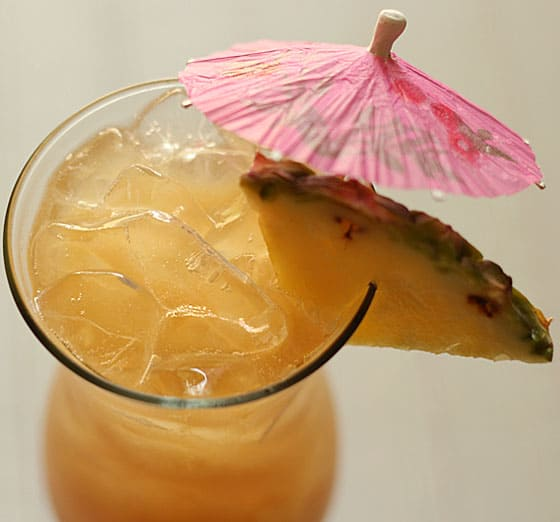 Top view of a yellow cocktail garnished with pineapple and a pink umbrella.
