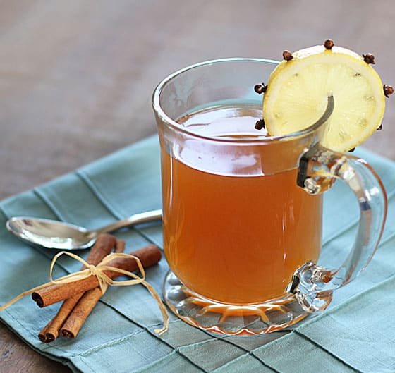 Hot toddy cocktail in a clear mug garnished with lemon