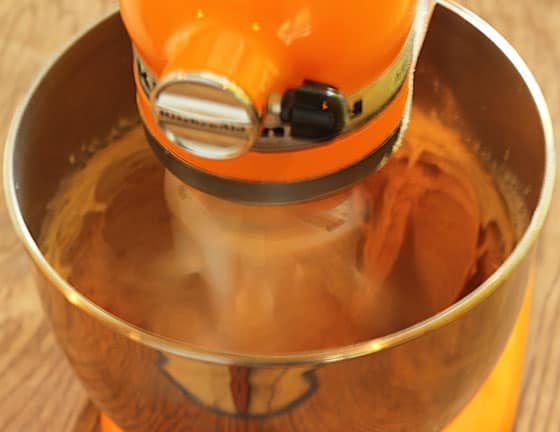 An orange stand mixer beating cookie dough in a stainless bowl.