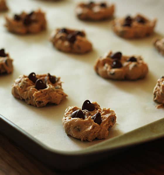 Unbaked cookies (cookie dough) on a baking sheet lined with parchment paper.