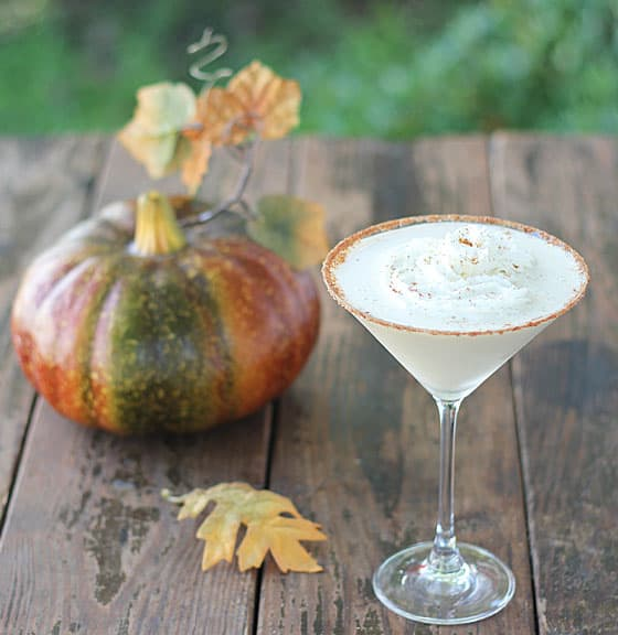 A cocktail in a martini glass on a wood surface.  A decorative pumpkin is in background.