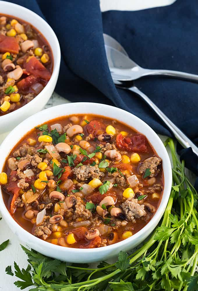 A closeup view of sausage stew with black eyed peas and corn in a white bowl.