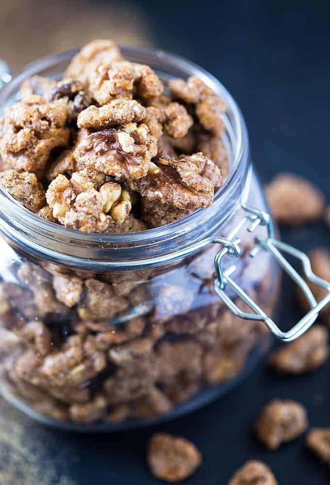Candied walnuts in a glass canister on a dark surface.