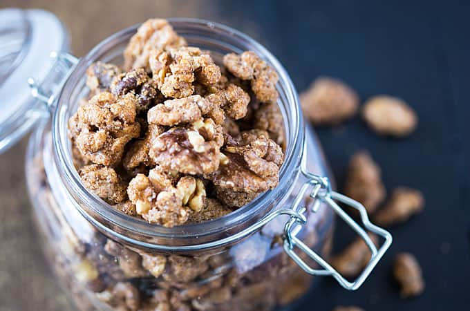 Overhead view of an open glass canister filled with candied walnuts.
