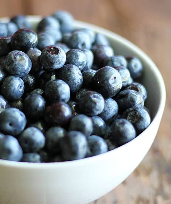 A closeup of fresh blueberries in a white bowl.