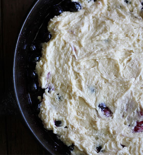 Overhead view of unbaked cobbler mixture spread over blueberries in a cast iron skillet.