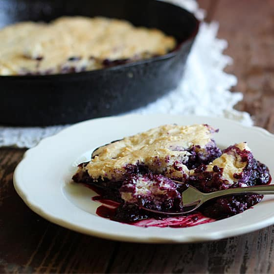 Blueberry cobbler on a white plate with a spoon. A skillet is in the background.
