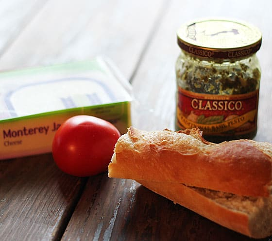A pack of cheese, a tomato, sliced baguette and a jar of pesto on a wood surface.
