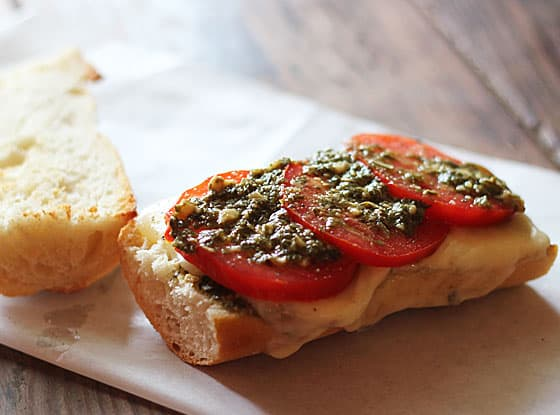 A sliced baguette topped with sliced tomatoes and pesto on a piece of parchment paper.