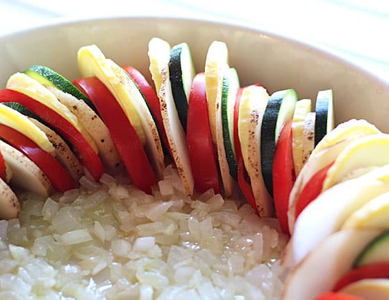 Closeup view of thinly sliced vegetables arranged in a baking dish with chopped onions.
