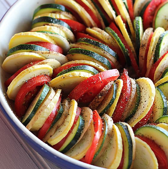 Thinly sliced squash, tomatoes and potatoes arranged in a baking dish.