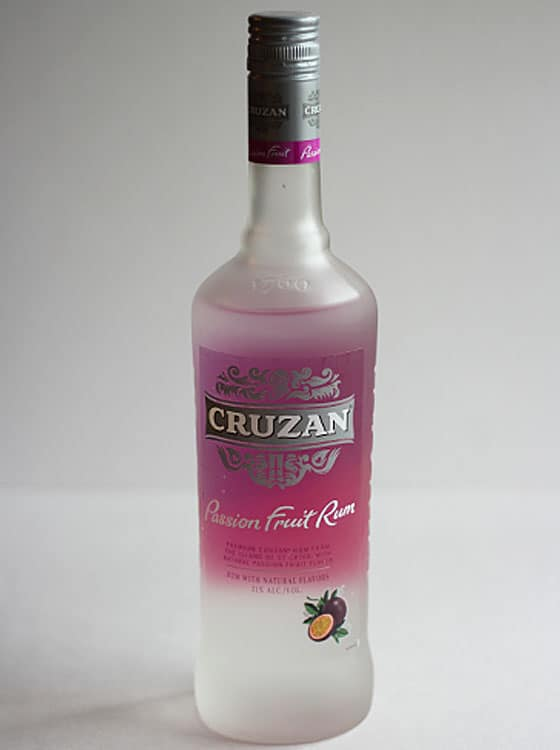 A bottle of rum on a white surface and gray background.