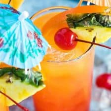 An orange cocktail in a glass garnished with a cherry, pineapple, orange and an umbrella.