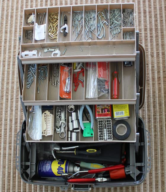 Overhead view of an opened tackle box with nails and other household tools in the compartments.