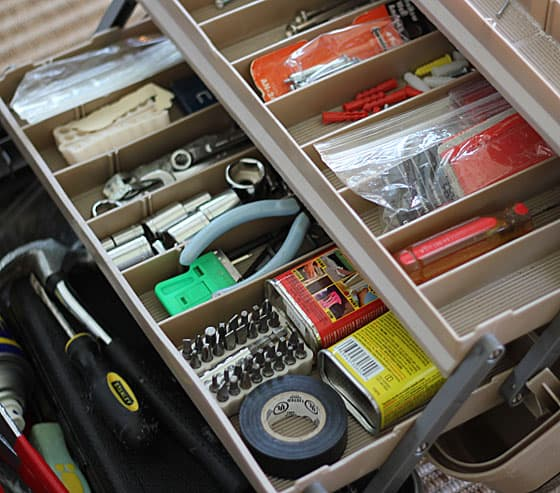 An opened tackle box with household tools in it.