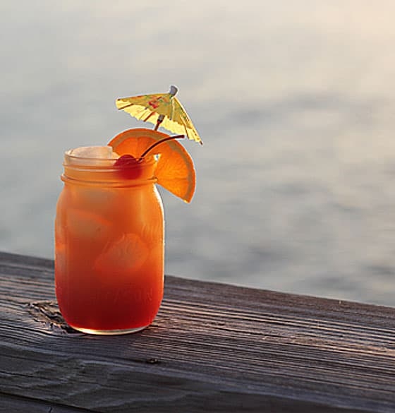 Rum Punch cocktail in a glass garnished with an orange slice and maraschino cherry