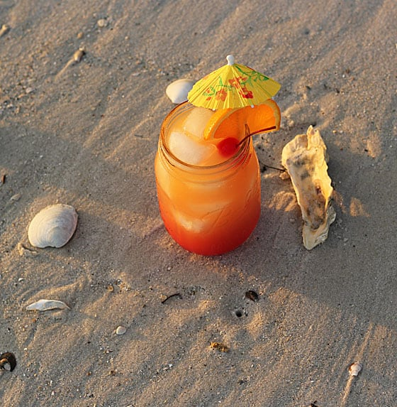 Rum Punch drink in a mason jar in the sand on the beach