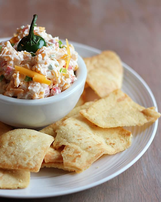 Pimento cheese topped with a jalapeno stem in a white bowl surrounded by chips.